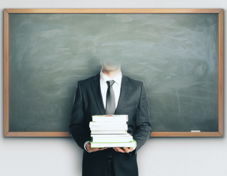 Headless businessman with books on chalkboard background. Knowledge concept Stock Photo