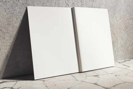 Side view of open white hardcover notebook leaning on concrete wall. Abstract supplies, stationery items. Mock up, 3D Rendering