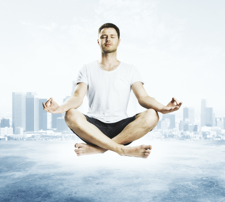 Meditating young european man on abstract city background. Relaxation and lifestyle concept