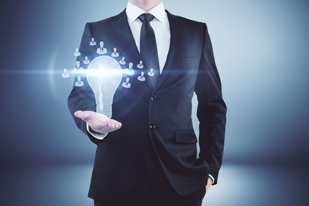 Businessman holding glowing lamp with hr icons in abstract gradient interior. Human resources concept