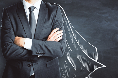 Businessman with drawn cape on chalkboard wall background. Protection concept