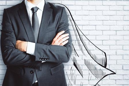 レンガ壁の背景に描かれた岬で実業家。リーダーシップの概念