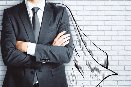 Businessman with drawn cape on brick wall background. Leadership concept Фото со стока