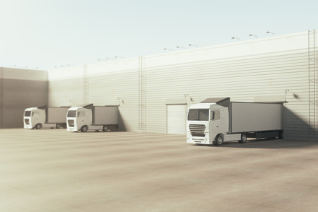 Facade of an industrial building and warehouse with freight cars parked parallelly under bright blue sky. Advertising copy space. Cargo concept. 3D Rendering Stock Photo