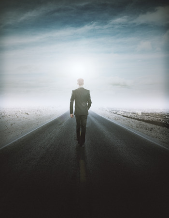Back view of young businessman walking on road. Success concept