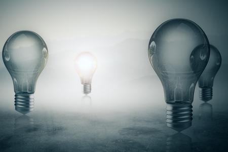 Glowing light bulbs on misty blurry gray background. Achievement concept. 3D Rendering Reklamní fotografie