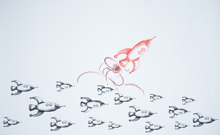 chasing: Think differently. Different drawn rocket ship on white wall background. Leader and startup concept
