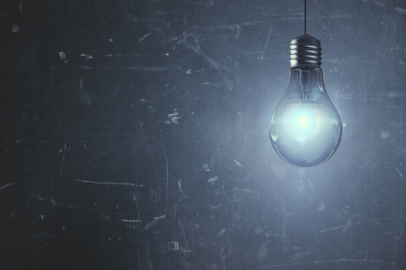 glass reflection: Glowing light bulb on aged concrete wall background with copy space. Solution concept. 3D Rendering