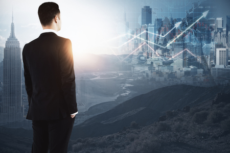 Side view of young businessman looking at abstract New York city view forex chart and sunlight. Fund management concept