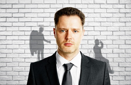 Man with angel and demon shadows on white brick wall background. True personality concept