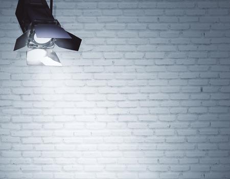 Spotlight illuminating empty brick wall. Professional lighting equipment concept. Mock up, 3D Rendering