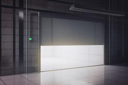 warehouse building: Side view of new tile interior with illuminated opening garage door. Mock up, 3D Rendering Stock Photo