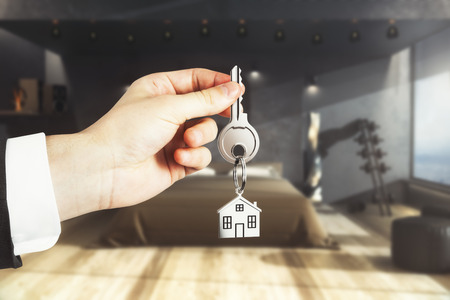 Close up of businessman hand holding key with house keychain on blurry bedroom interior background. Real estate concept. 3D Rendering Stock Photo
