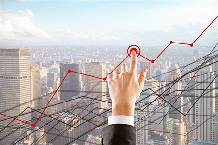 Hand pointing at abstract business charts on bright city background. Finance concept