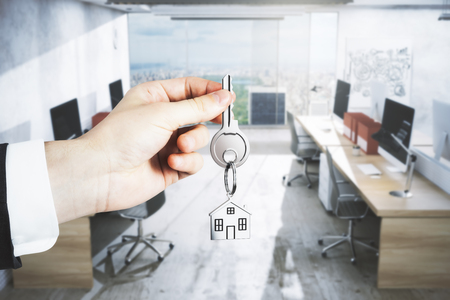 Businessman hand holding key with house keychain on blurry office interior background. Landlord concept. 3D Rendering