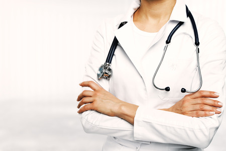 Unrecognizable female doctor with stethoscope and folded arms standing on blurry white background with copy space. Medicine and cardiology concept Stock Photo