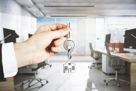 Businessman hand holding key with house keychain on blurry office interior background. Rent concept. 3D Rendering