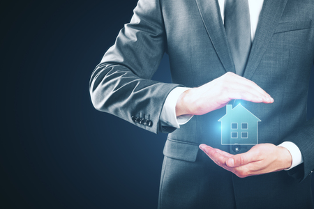 Businessman holding creative glowing house icon on blue background. Real estate concept Stock Photo