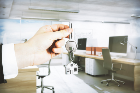 Businessman hand holding key with house keychain on blurry office interior background. Real estate concept. 3D Rendering