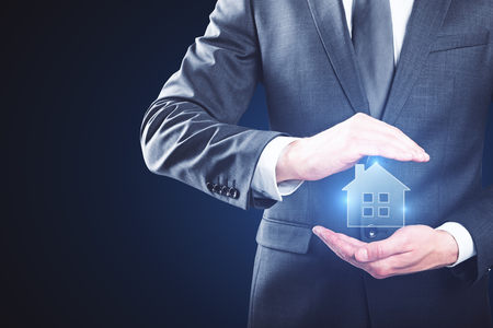 Businessman holding creative glowing house icon on blue background. Mortgage concept Imagens - 84395709