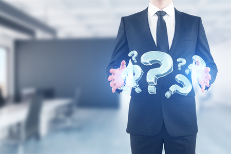 Businessman holding abstract glowing question marks in blurry office interior. Inquiry concept. 3D Rendering Фото со стока