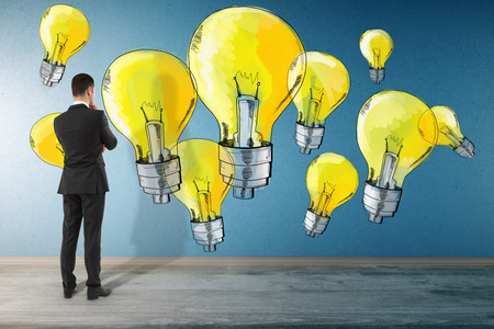 Back view of thoughtful young businessman in interior looking at concrete wall with drawn yellow light bulbs. Idea and energy concept