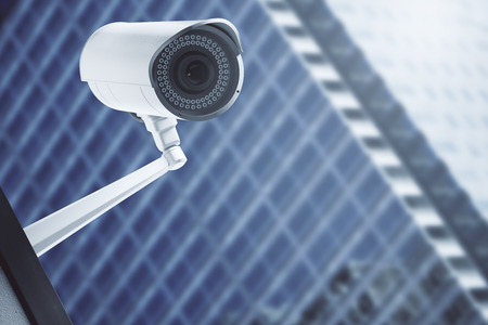 Close up of CCTV camera with blurry modern glass building in the background. Spy concept. 3D Rendering