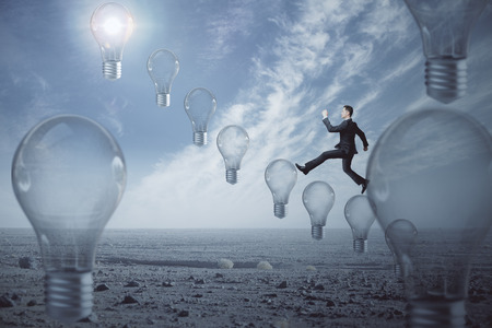 Side view of businessman climbing abstract light bulb ladder on creative sky background. Idea and innovation concept. 3D Rendering Stock Photo