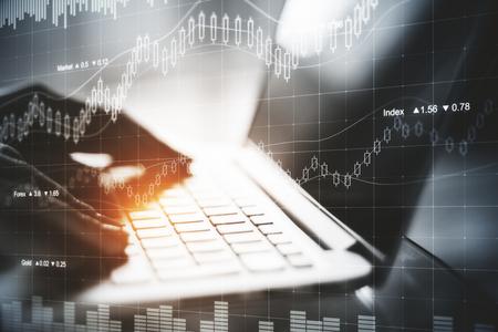 Hand die laptop met abstract forex hologram met behulp van. Financiën concept. Economisch beeld. Dubbele blootstelling Stockfoto