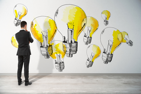 Back view of thoughtful young businessman in interior looking at concrete wall with drawn yellow light bulbs. Idea and success concept Stock Photo