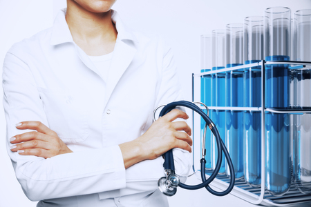 Female doctor with stethoscope and flasks with blue liquid. Medical research concept