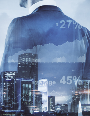 Unrecognizable businessman on abstract city background with business chart. Financial growth concept. Double exposure