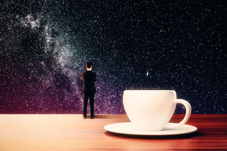 Back view of abstract thoughtful tiny businessman standing on wooden desktop with coffee cup on saucer and looking at space night sky. Creativity concept. 3D Rendering Stok Fotoğraf