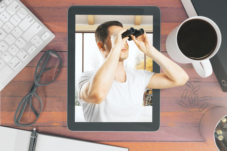 Top view of wooden desktop with abstract businessman using binoculars on tablet screen, coffee cup, keyboard and other items. Research concept. 3D Rendering Stock fotó