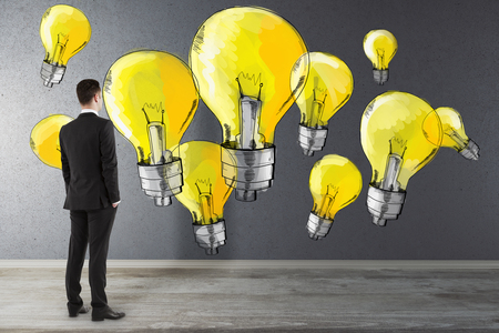 Back view of thoughtful young businessman in interior looking at concrete wall with drawn yellow light bulbs. Idea and power concept Stock Photo