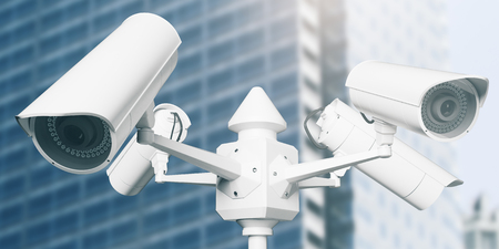 White street CCTV cameras with blurry glass building in the background. Safety concept. 3D Rendering