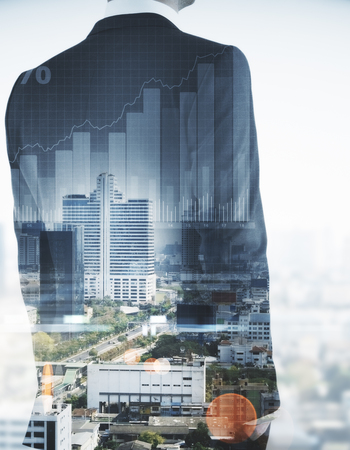 Unrecognizable businessman on abstract city background with business chart. Finance concept. Double exposure Stock Photo