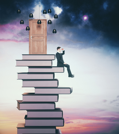 Side view of young businessman sitting on book pile with abstract door and looking into the distance on sky background. Abstraction concept. 3D Rendering Reklamní fotografie - 84779128