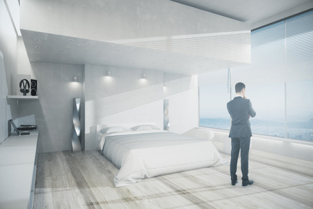 Side view of young businessman looking out of window in modern bedroom interior with white furniture, wooden floor and panoramic view. Think concept. 3D Rendering