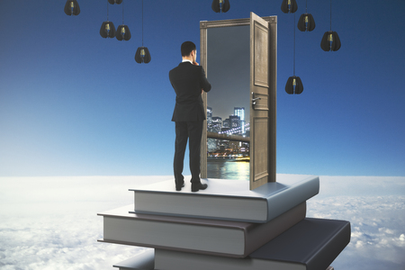 Back view of thoughtful young businessman standing on abstract book tower with open door on sky background. Knowledge concept. 3D Rendering