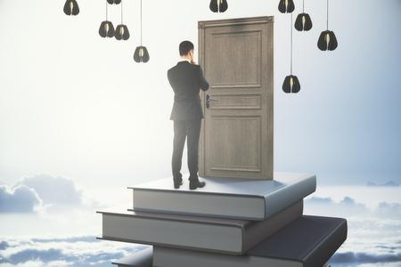 空の背景に閉じたドアを持つ抽象ブックタワーに立って思慮深い若いビジネスマンのバックビュー。チャレンジコンセプト。3D レンダリング 写真素材