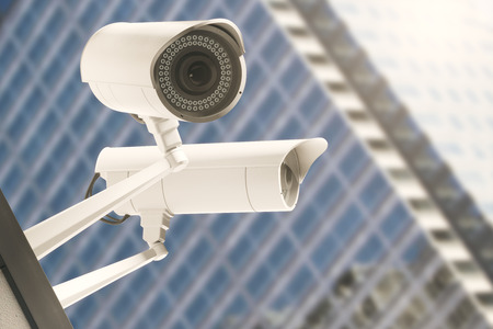 security monitor: Close up of CCTV cameras with blurry modern glass building in the background. Alertness concept. 3D Rendering