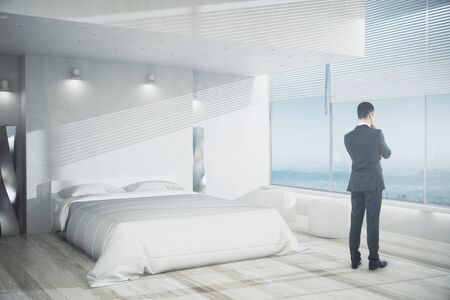 Side view of young businessman looking out of window in modern bedroom interior with white furniture, wooden floor and panoramic view. Research concept. 3D Rendering