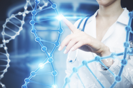 Female doctor pointing at abstract DNA hologram on blurry background. Science concept 스톡 콘텐츠