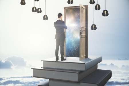 Back view of thoughtful young businessman standing on abstract book tower with open door on sky background. Leadership concept. 3D Rendering
