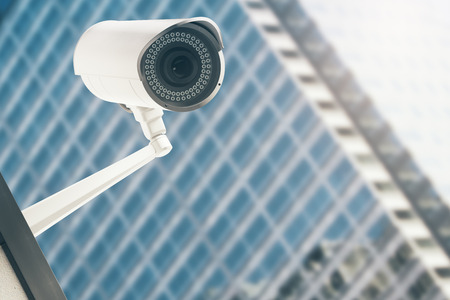 security monitor: Close up of CCTV camera with blurry modern glass building in the background. Video concept. 3D Rendering
