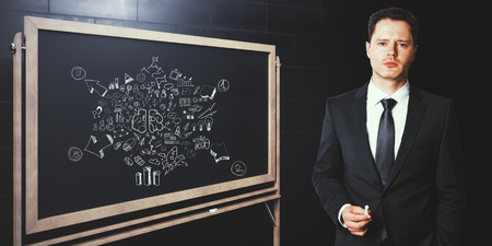 Attractive caucasian businessman drawing business sketch on chalkboard. Concrete wall background. Seminar concept. 3D Rendering