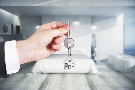 Hand met sleutel in moderne slaapkamer interieur. Onroerend goed, hypotheekconcept. 3D-weergave