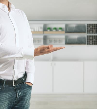 De hand van de mens presenteert wazig keuken interieur met tellers en apparatuur. Huurder concept. 3D-rendering