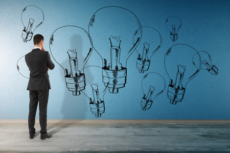 Back view of thoughtful young businessman in interior looking at concrete wall with drawn lamps.. Idea and imagination concept Stock Photo
